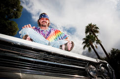 Hippie on a car Hood Stock Images