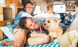 Hippie couple with funny dog traveling together on vintage minivan transport - Life inspiration concept with indie people on mini. Van adventure trip in relax stock photo