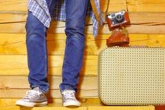 Hippie dans les jeans et des espadrilles avec une valise et un appareil-photo Image stock