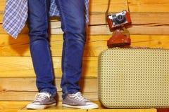 Hippie dans les jeans et des espadrilles avec une valise et un appareil-photo Images libres de droits
