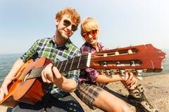 Hippie de jeune homme jouant la guitare pour la femme Images libres de droits