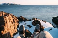 Hippie, der auf Klippe vor Bruch über See- und Schneebergen sitzt Pov-Ansicht von Beinen und von Schuhen auf dem blauen Wasser de lizenzfreies stockbild