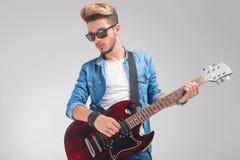 Hippie, der die Gitarre im Studiohintergrund spielt Stockfotos