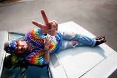 Hippie en el capo motor de un coche Fotos de archivo libres de regalías