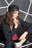 Hippie féminin dans le costume noir surdimensionné Modelez avec le sembler réfléchi se reposant sur le divan en cuir Veste de por Photo libre de droits