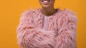 Hippie féminin moderne dans des mains de croisement de manteau de fourrure de fond jaune rose de position banque de vidéos