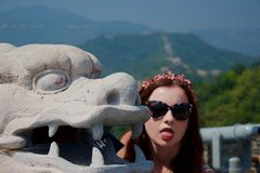 Western hippie girl tourist posing with Chinese dragon in mountains stock images
