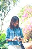 Hippie-Frau, die Fotos mit Retro- Filmkamera im Blumenkaimanfisch macht stockbild