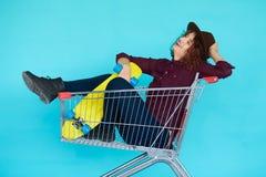 Hippie-Frau mit dem gelben Skateboard, das in der Einkaufslaufkatze sitzt Lizenzfreies Stockbild