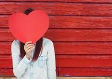 Hippie-Frau mit dem Gesicht bedeckt mit einem Herzen Roter hölzerner Hintergrund Stockbild