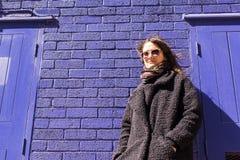 Hippie-Frau mit der Sonnenbrille, die vor violetter Wand steht Lizenzfreie Stockfotos