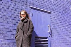 Hippie-Frau mit der Sonnenbrille, die vor violetter Wand steht Stockbild