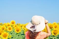 Hippie-Frau mit Strohhut auf dem Gebiet von Sonnenblumen Reisemädchen genießen Sommersonnenuntergang auf dem Gebiet von Sonnenblu Stockbild