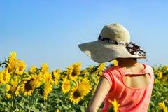 Hippie-Frau mit Strohhut auf dem Gebiet von Sonnenblumen Reisemädchen genießen Sommersonnenuntergang auf dem Gebiet von Sonnenblu Lizenzfreie Stockbilder
