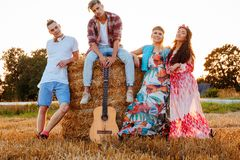 Hippie friends with guitar in a wheat field stock photo