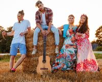 Hippie friends with guitar in a wheat field royalty free stock image