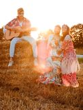 Hippie friends with guitar in a wheat field stock photos