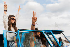 Hippie friends at minivan car showing peace sign Royalty Free Stock Photos