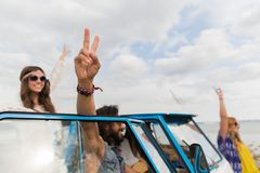 Hippie friends at minivan car showing peace sign Stock Image