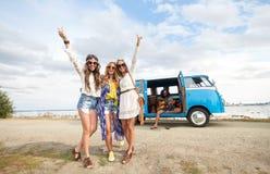 Hippie friends near minivan car showing peace sign Stock Images