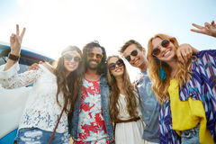 Hippie friends over minivan car showing peace sign. Summer holidays, road trip, vacation, travel and people concept - smiling young hippie friends over minivan stock photo