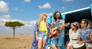 Hippie friends playing music at minivan in africa. Summer holidays, road trip, travel and people concept - happy young hippie friends with guitar and drum Stock Photos