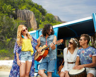 Hippie friends playing music at minivan on beach. Summer holidays, road trip, travel and people concept - happy young hippie friends with guitar and drum playing Royalty Free Stock Photography