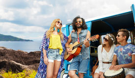 Hippie friends playing music at minivan on island. Summer holidays, road trip, travel and people concept - happy young hippie friends with guitar and drum Stock Photography