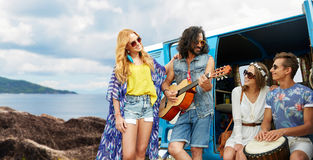 Hippie friends playing music at minivan on island. Summer holidays, road trip, travel and people concept - happy young hippie friends with guitar and drum Royalty Free Stock Images