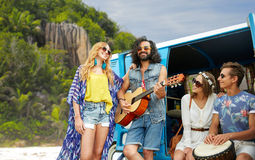 Hippie friends playing music at minivan on island. Summer holidays, road trip, travel and people concept - happy young hippie friends with guitar and drum Stock Images