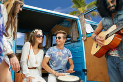 Hippie friends playing music over minivan on beach. Summer holidays, road trip, travel and people concept - happy young hippie friends having fun and playing Stock Photo