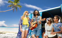 Hippie friends playing music over minivan on beach. Summer holidays, road trip, travel and people concept - happy young hippie friends having fun and playing Royalty Free Stock Photo