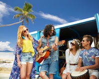 Hippie friends playing music over minivan on beach. Summer holidays, road trip, travel and people concept - happy young hippie friends having fun and playing Stock Photography