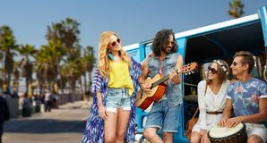 Hippie friends playing music over minivan in la. Summer holidays, road trip, travel and vacation concept - happy young hippie friends having fun and playing Stock Photo