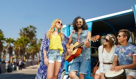 Hippie friends playing music over minivan in la. Summer holidays, road trip, travel and vacation concept - happy young hippie friends having fun and playing Royalty Free Stock Images