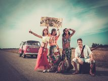Hippie friends on a road trip. Multinational hippie hitchhikers with guitar and luggage on a road Royalty Free Stock Photo