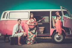 Hippie friends on a road trip. Young hippie friends with guitar on a road trip stock photo