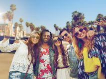 Hippie friends showing peace over venice beach. Summer holidays, vacation, travel and people concept - smiling young hippie friends showing peace hand sign over Royalty Free Stock Photography