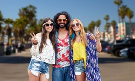 Hippie friends showing peace at venice beach in la. Summer holidays, youth culture, gesture and people concept - smiling young hippie friends in sunglasses Royalty Free Stock Photography