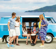 Hippie friends with tom-tom playing music over car. Summer holidays, road trip, travel and people concept - happy young hippie friends with tom-tom drum playing Royalty Free Stock Photos