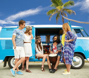 Hippie friends with tom-tom playing music over car. Summer holidays, road trip, travel and people concept - happy young hippie friends with tom-tom drum playing Royalty Free Stock Image