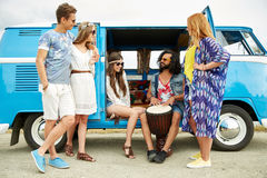 Hippie friends with tom-tom playing music over car Royalty Free Stock Photos