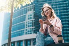 Hippie-Geschäftsfrau in den Gläsern sitzt draußen und benutzt Smartphone Ist in der Nähe Tasse Kaffee Im Hintergrund ist Wolkenkr Stockbild