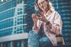 Hippie-Geschäftsfrau in den Gläsern sitzt draußen und benutzt Smartphone Ist in der Nähe Tasse Kaffee Im Hintergrund ist Wolkenkr Lizenzfreies Stockfoto