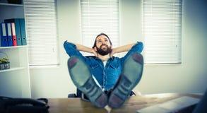 Hippie-Geschäftsmann, der an seinem Schreibtisch sich entspannt Stockbild