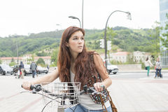 Hippie girl with bicycle in the street. Royalty Free Stock Photo
