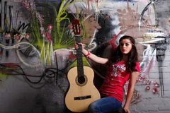 Hippie girl with guitar. In front of a graffiti brick wall, looking straight stock photo