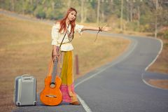 Hippie girl hitchhiking Stock Image