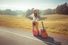 Hippie girl hitchhiking Stock Photo