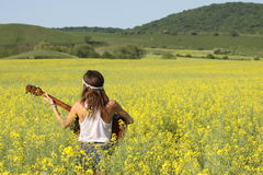 Hippie girl. Girl with hippie outfit playing guitar in a rapeseed field royalty free stock photography